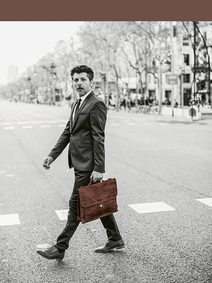 Geschäftsmann mit Ledertasche überquert eine Straße