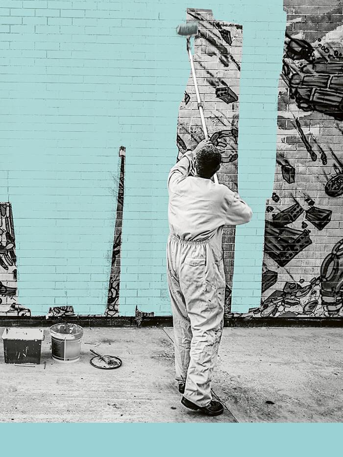 Mann überstreicht Graffiti mit Fassadenfarbe
